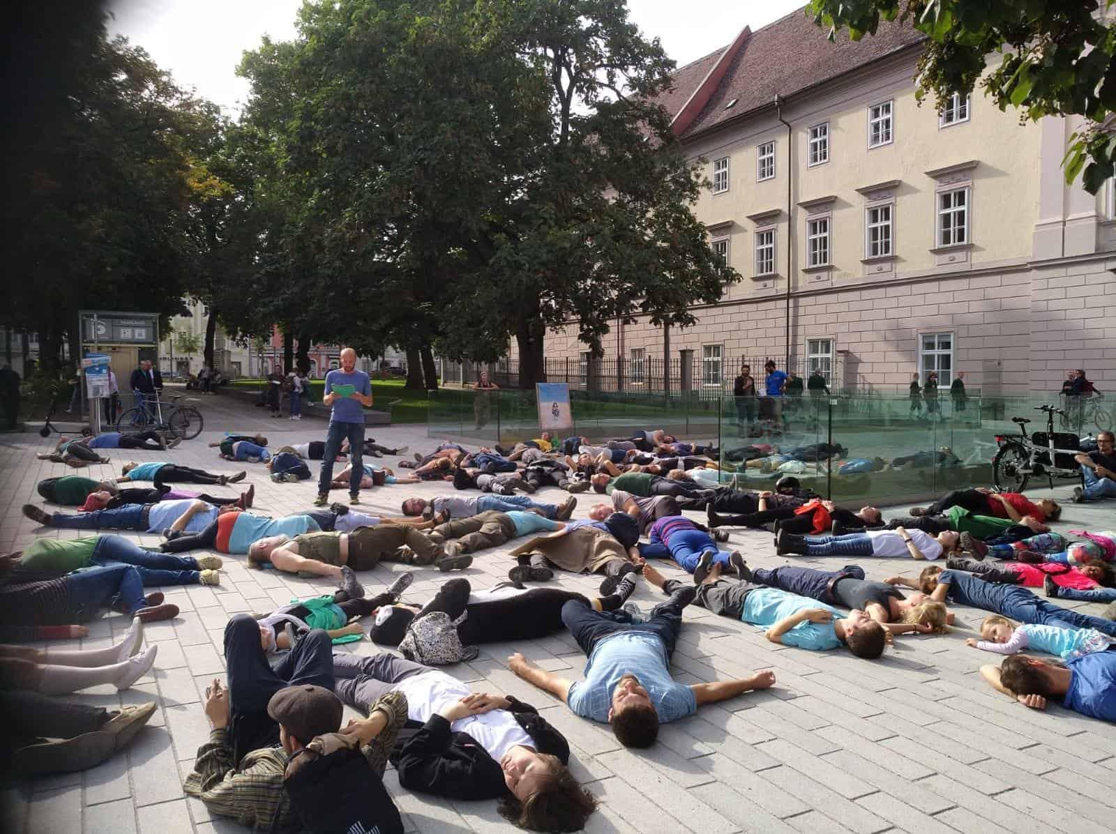 AktivistInnen und SympatisantInnen von XR Oberösterreich liegen vor dem Landhaus am Boden und symbolisieren damit das Artensterben und die Bedrohung durch die Klimakrise