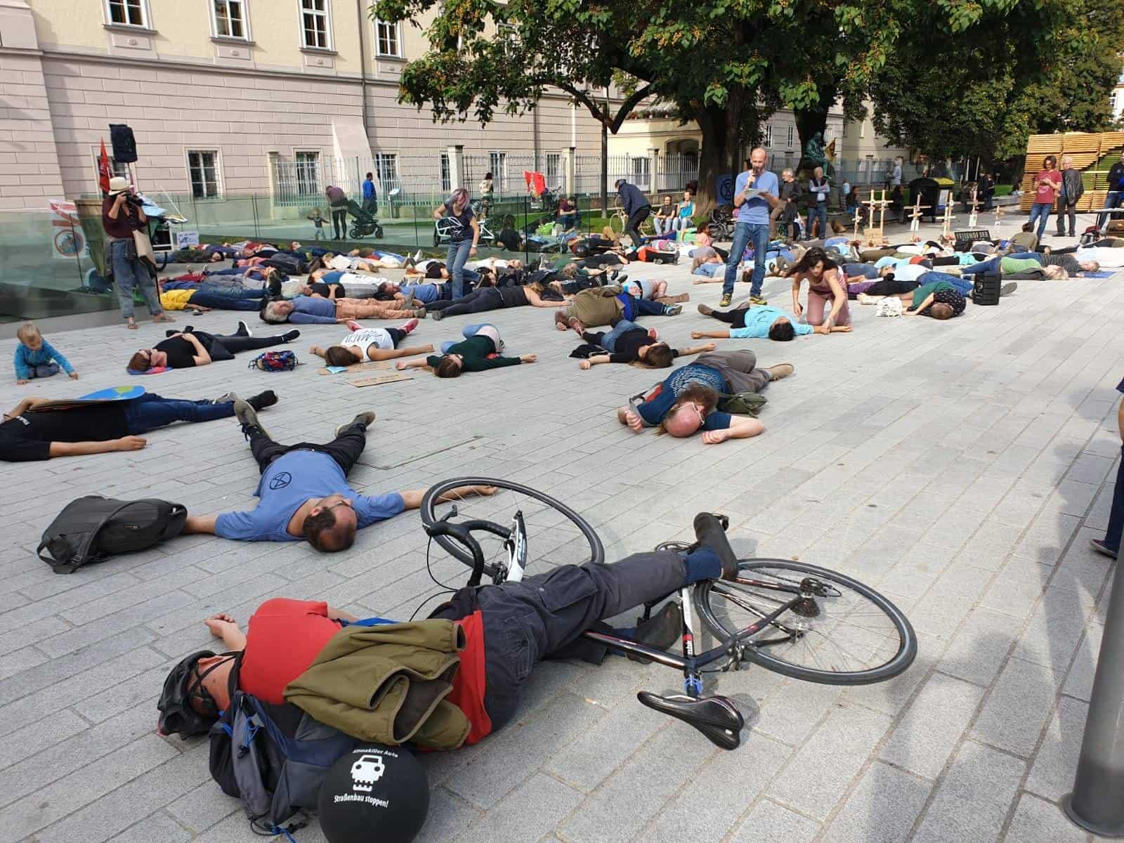 AktivistInnen und SympatisantInnen von XR Oberösterreich liegen vor dem Landhaus am Boden. Ein Aktivist hält eine Rede. Das Die in symbolisiert das Artensterben und die Bedrohung durch die Klimakrise