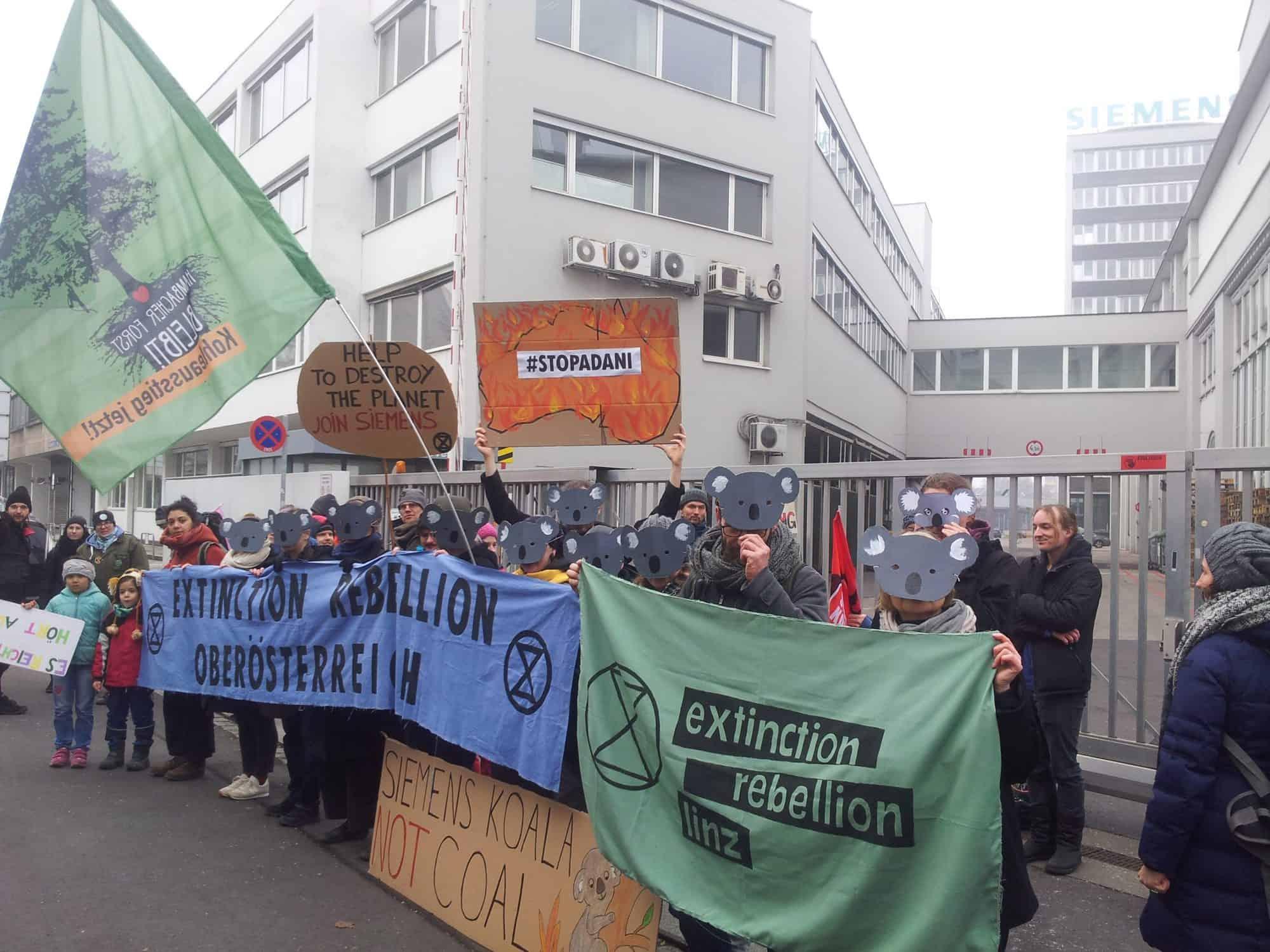 AktivistInnen verschiedener Gruppen demonstrieren vor der Siemens Zentrale in Linz gegen den Adani-Deal