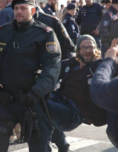 """Ein XR Aktivist wird von Polizisten weggetragen. Er hat in Wien während der Rebellion Week im Oktober 2019 in Wien im Rahmen der """"Aktion Erde"""" die Straße blockiert."""