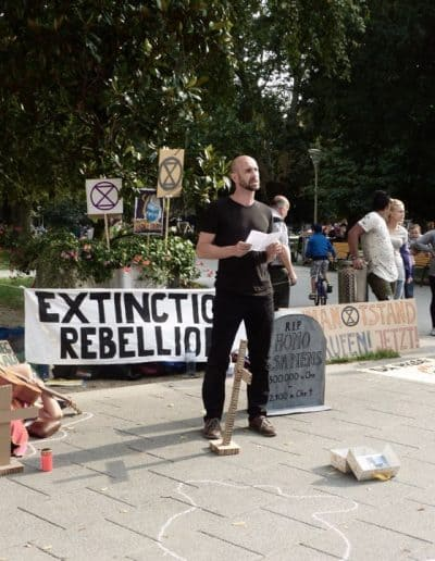 Ein Aktivist ält eine Rede während eines Die-Ins am Volksgarten