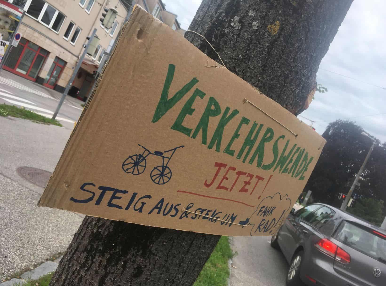 Ein Baum hält ein Schild und demonstriert für eine Verkehrswende (Aktion #aufbäumen)