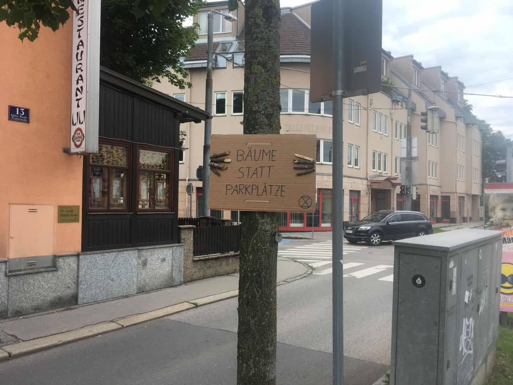 Ein Baum hält ein Schild und demonstriert für Bäume anstatt Parkplätzen (Aktion #aufbäumen)